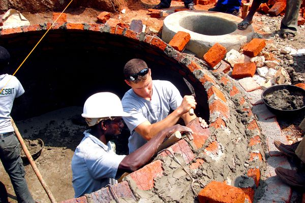 Cadet Ethan Dewart works with Ugandan construction worker to build a biogas digester dome with brick and mortar
