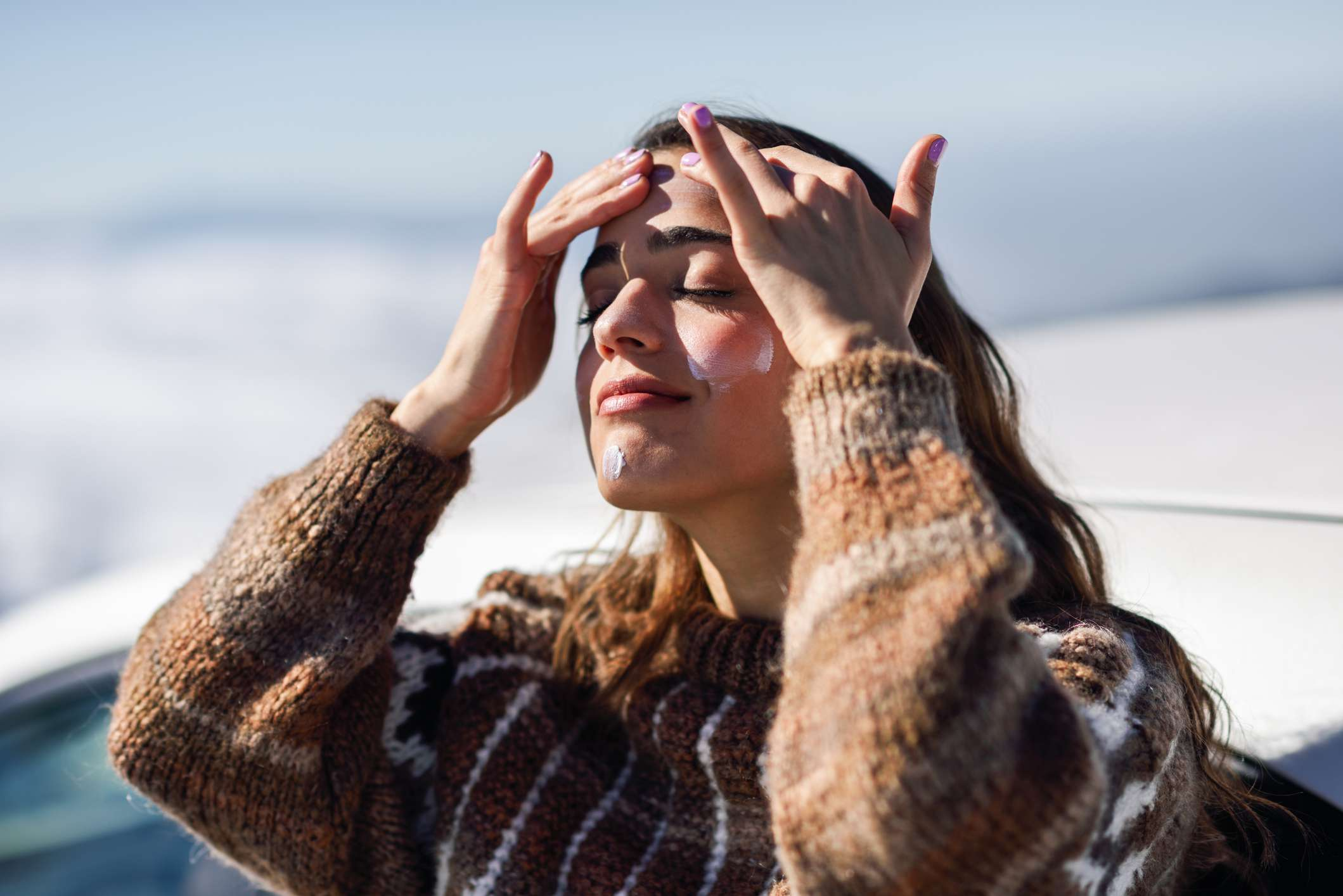 A woman applying sunscreen to her face outdoors.