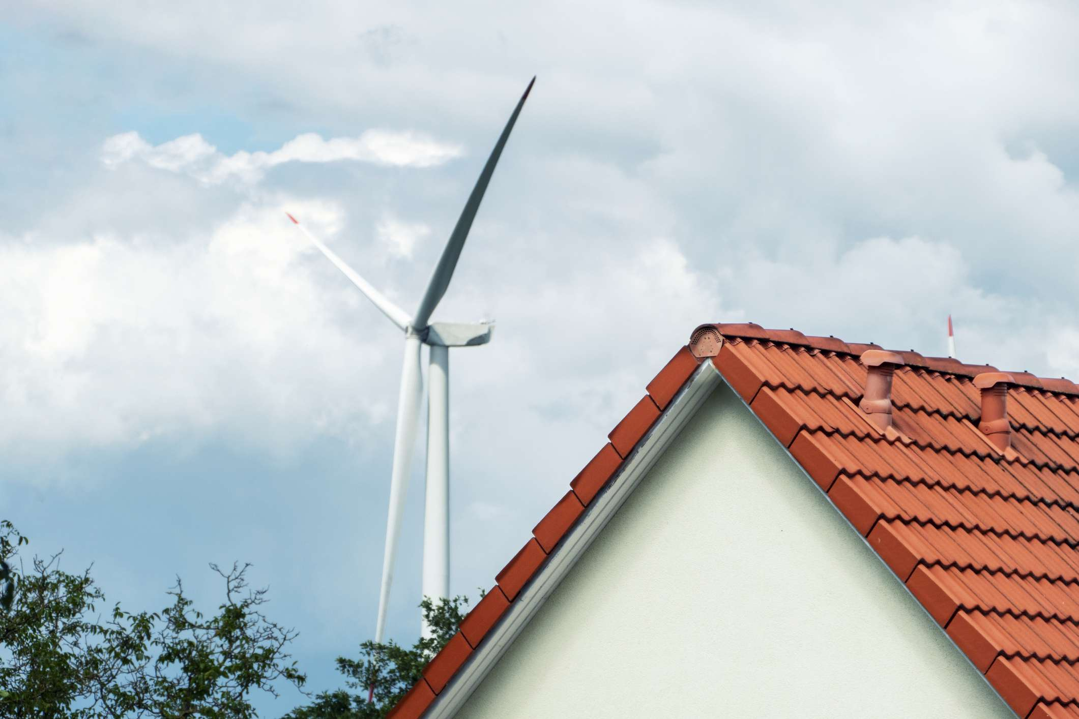 Wind turbine rising above trees and roof of a house