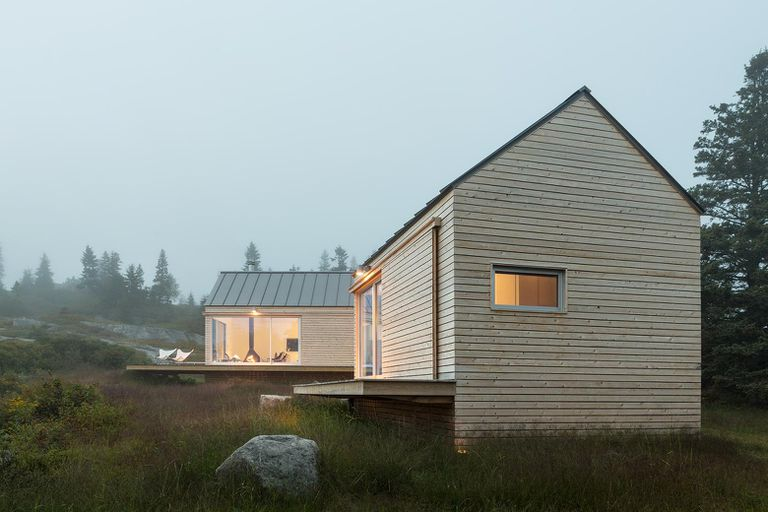 Wood-sided house surrounded by grassy fields and fog