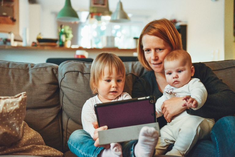 Mother, toddler and infant sitting on a couch, looking at digital tablet