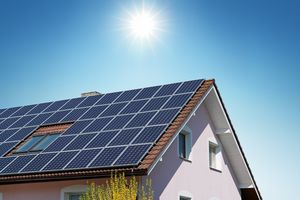 The sun shines on the roof of a home covered in solar panels.