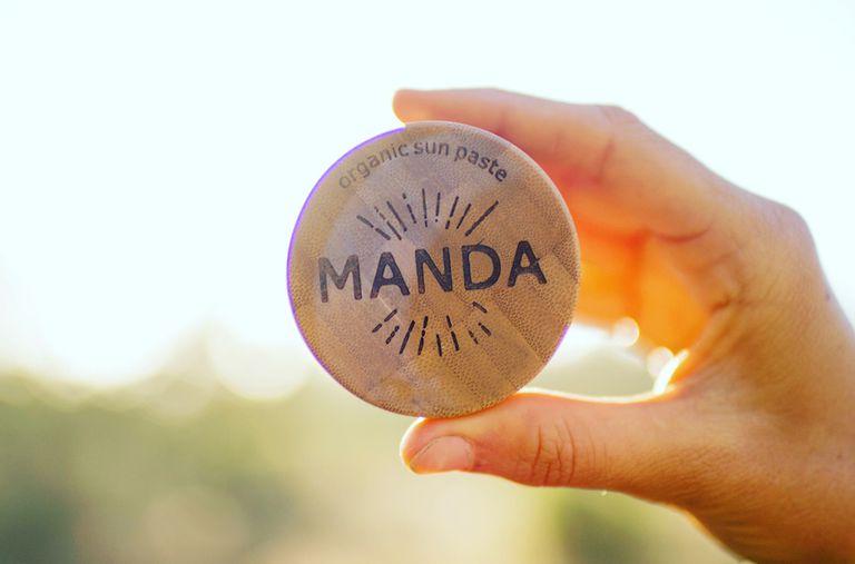 A hand holding up Manda organic sun paste outside.