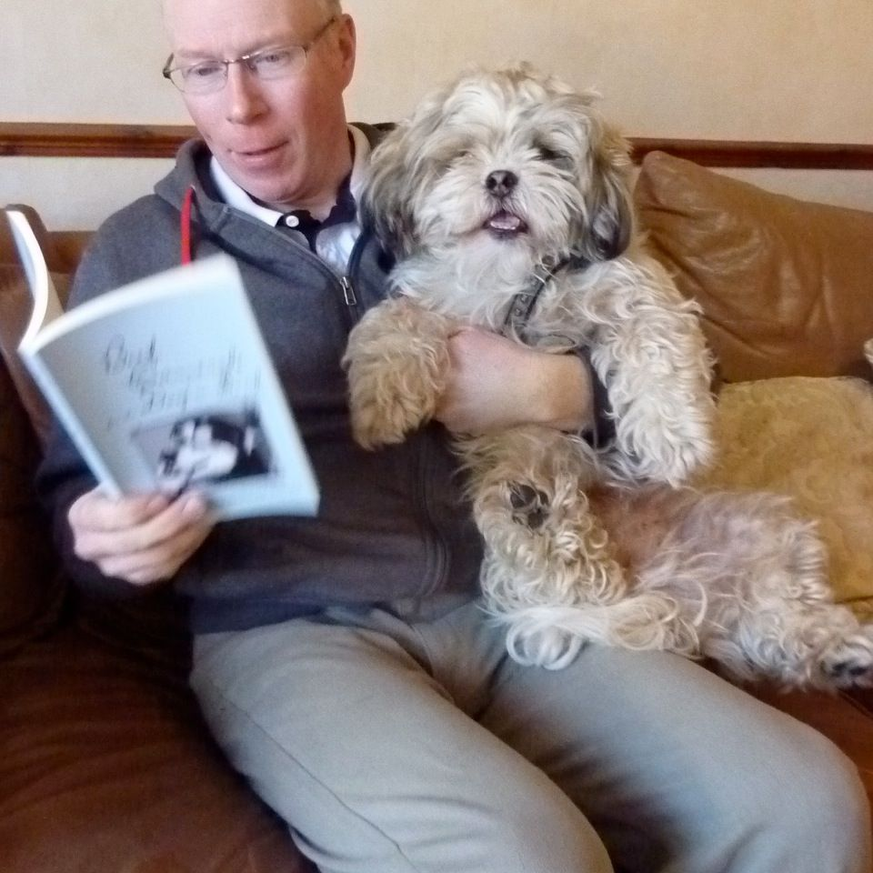 Man reading a book to a dog