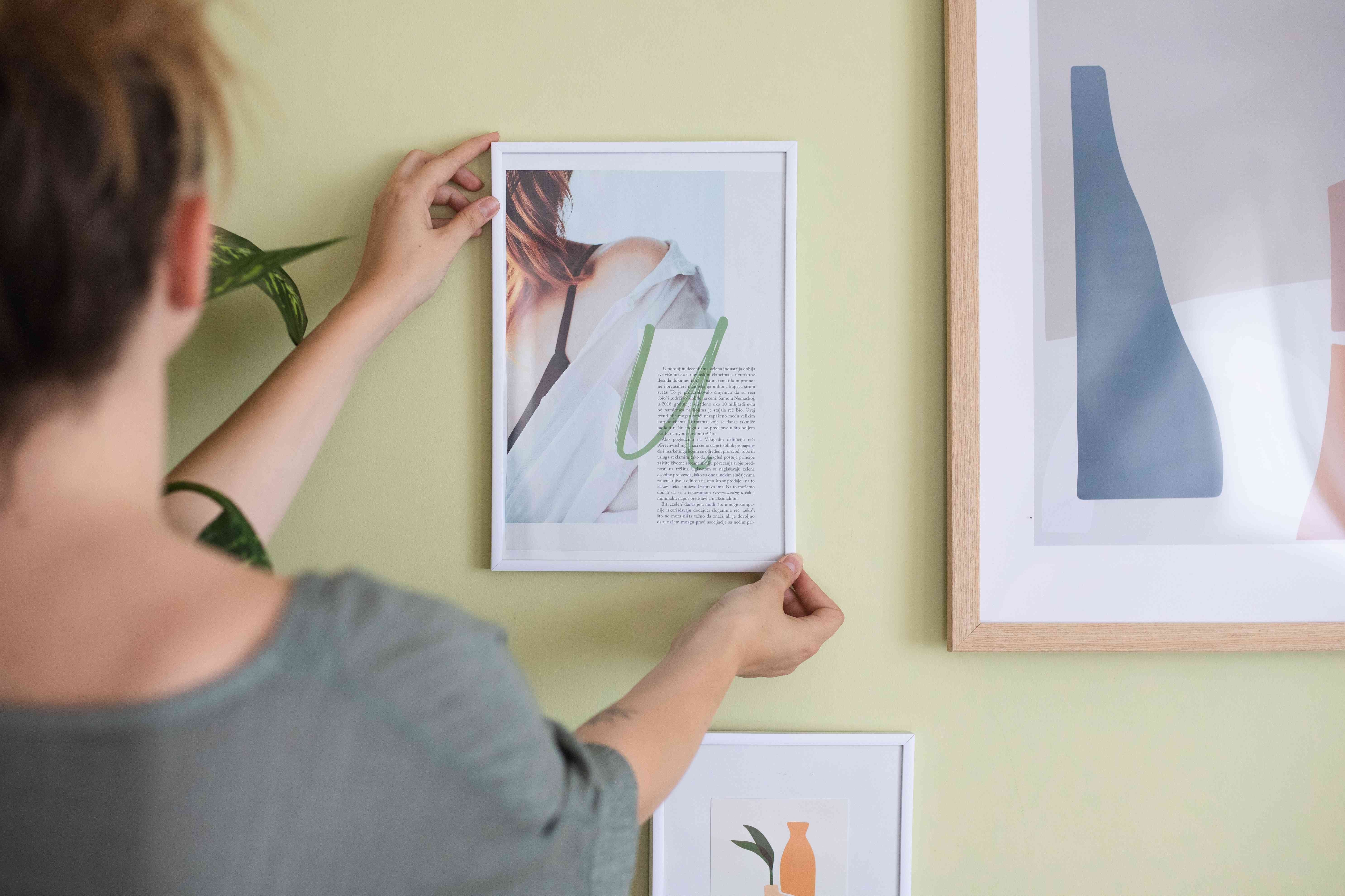 person hangs up framed piece of art cut out from magazine on pale green wall