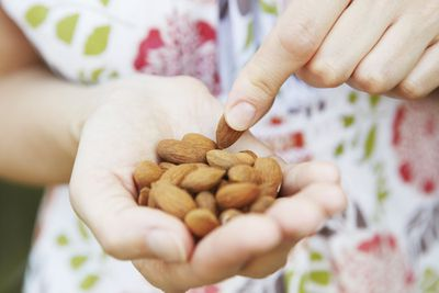 Person holding handful of nuts