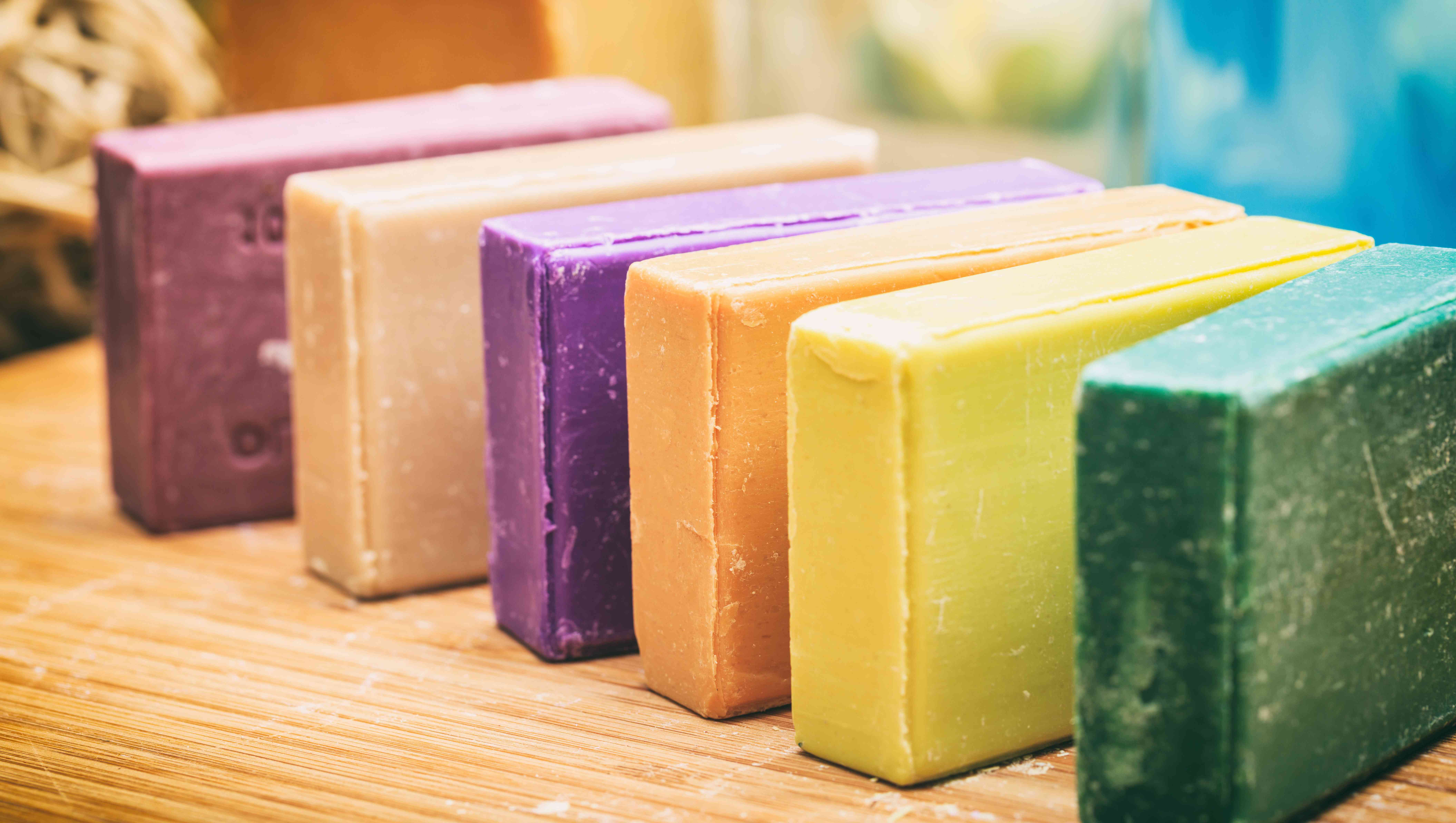 Rainbow display of colorful bar soaps on wooden background