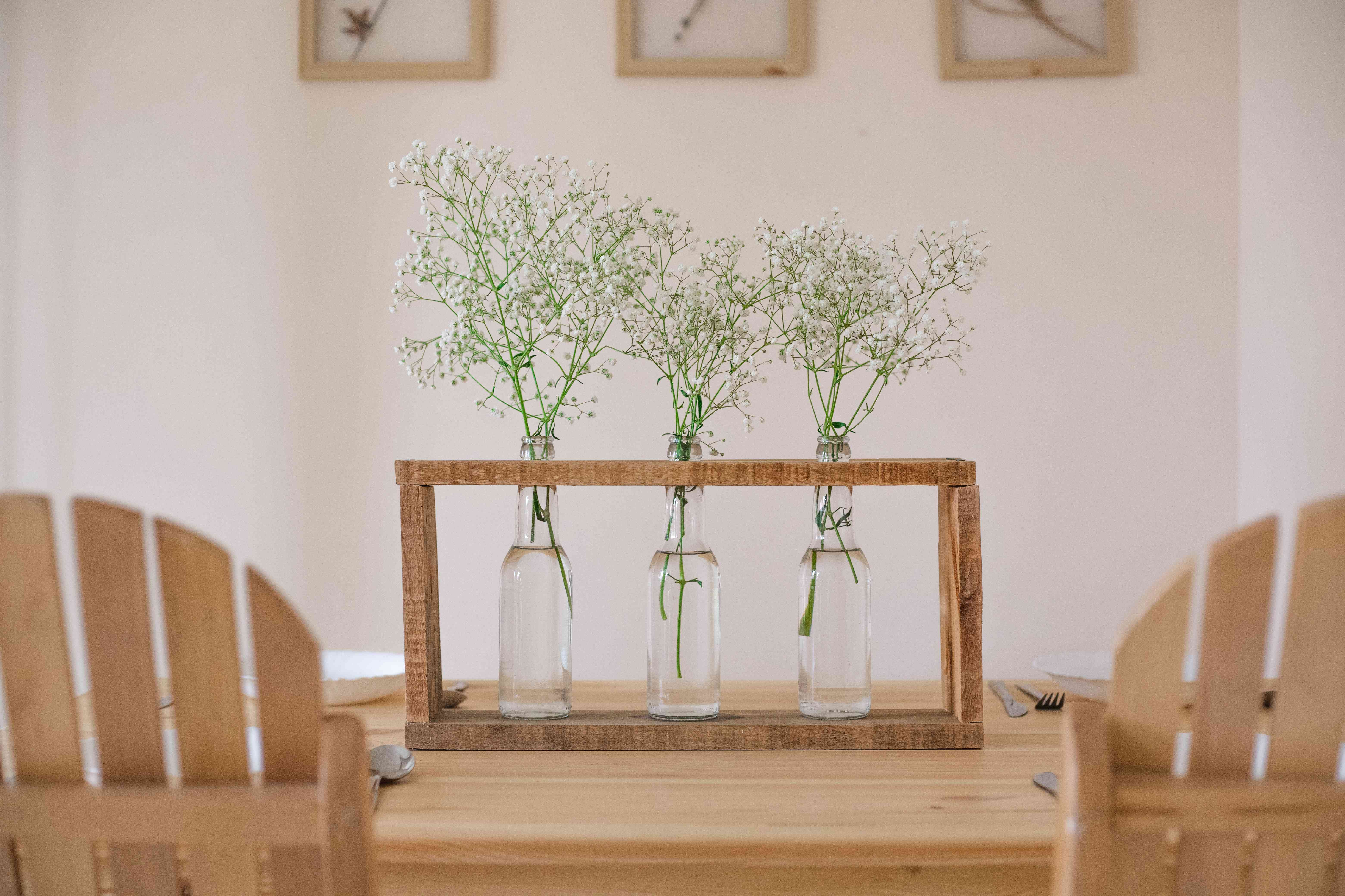 upcycled glass bottles as modern wood vase centerpiece with flowers on wooden table