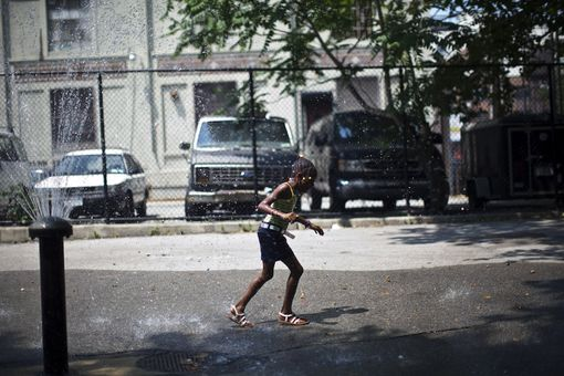 A girl runs through a water fountain to cool off in the Brooklyn borough of New York City