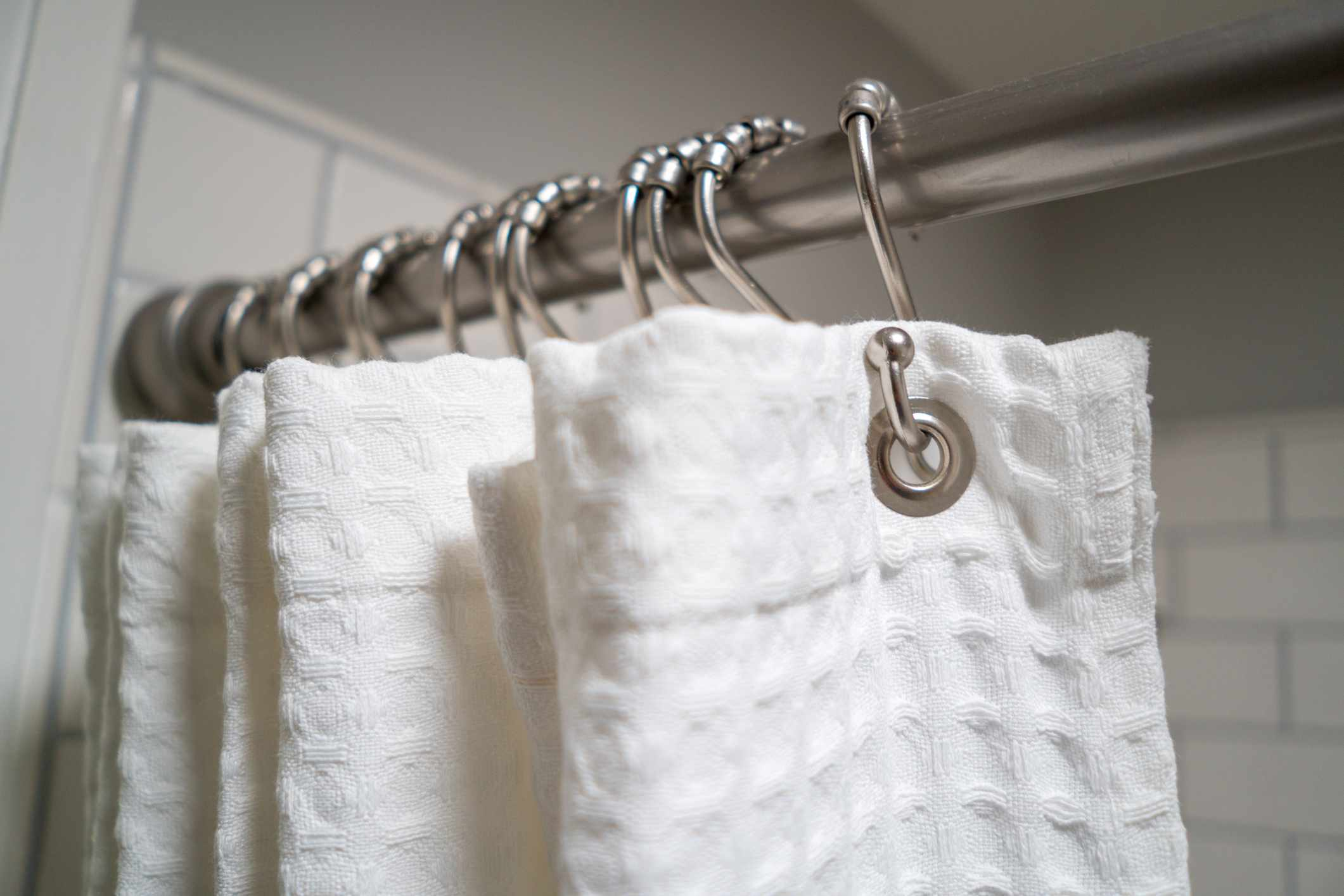 White cotton curtain hanging in a shower.
