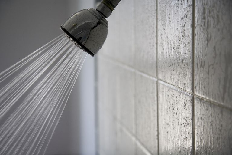 Silver showerhead with the water running against wet white tiles