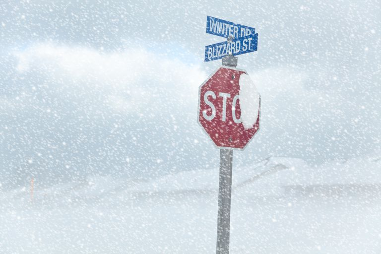 A stop sign at Winter Drive and Blizzard Street in a blizzard.