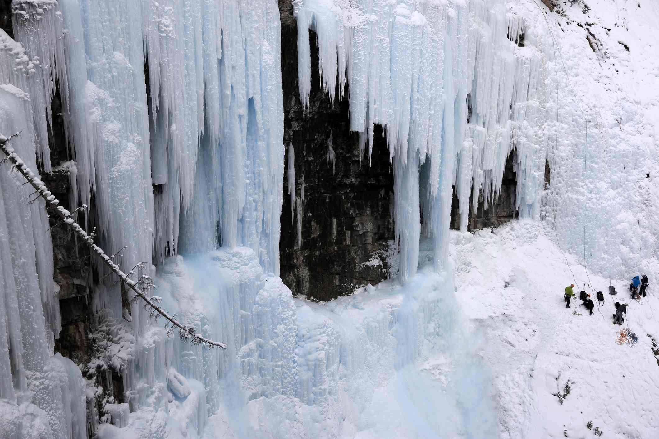 Ice climbers gathered at the base of frozen waterfalls