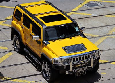 A yellow Hummer H3 in a parking lot.