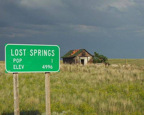 Lost Springs town sign with a small house in the background