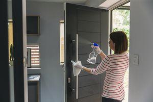 woman cleaning a metal door handle
