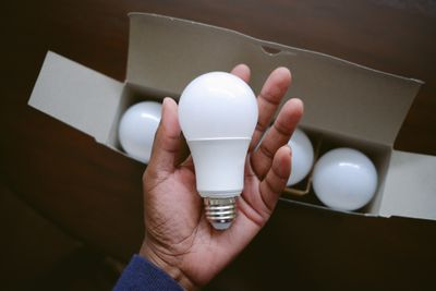 hand holds LED bulb in palm above a box of new lightbulbs