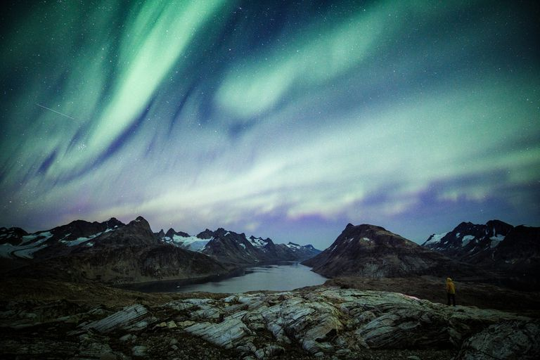 Green and purple northern lights over Greenland fjord