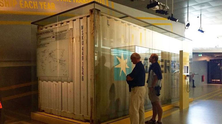 Two men looking at a shipping container encased in glass