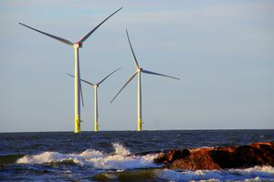 Wind turbines in the sea against a blue sky.