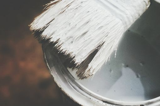 High Angle View Of Brush Over White Paint Can