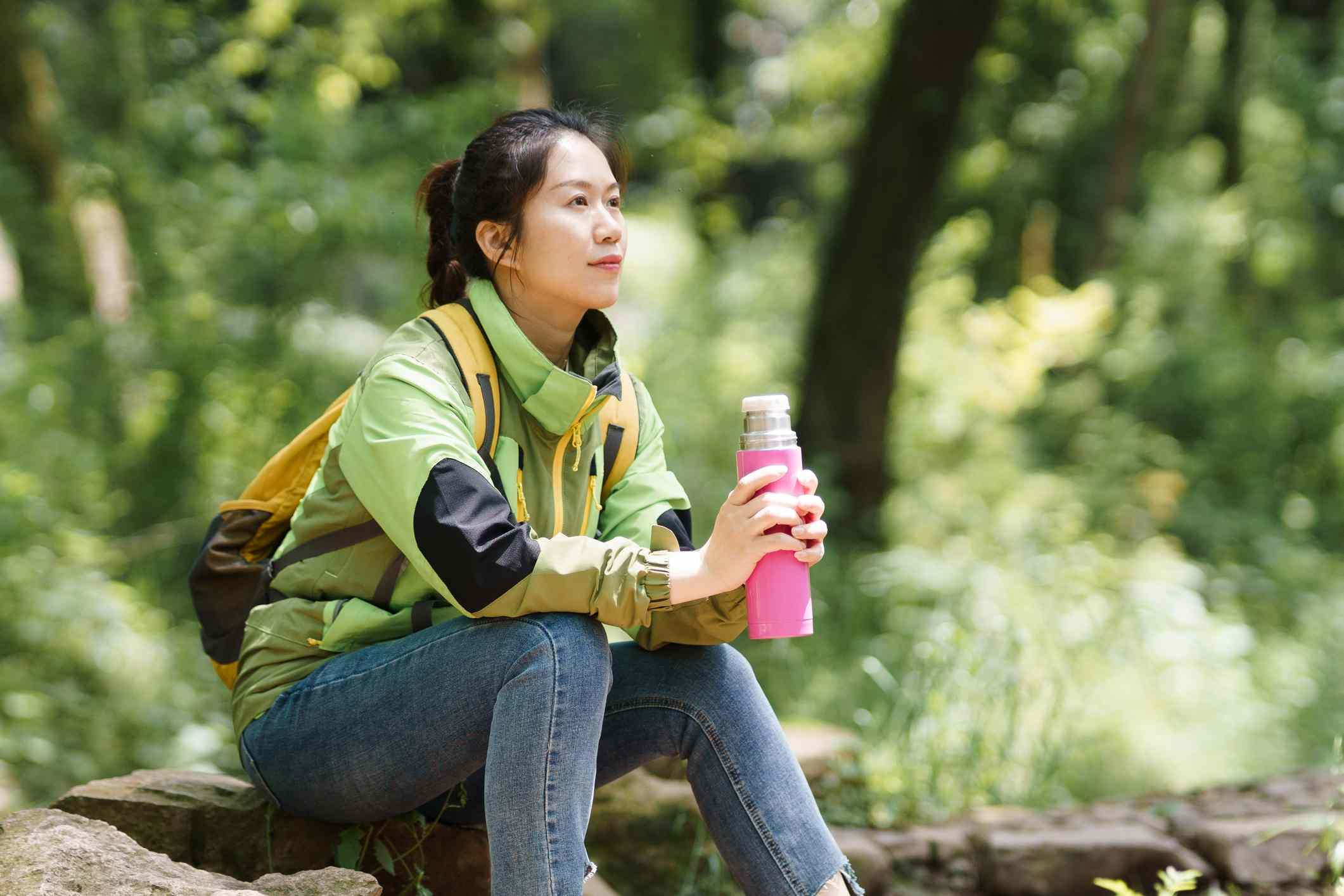 Hiker taking a break with reusable water bottle