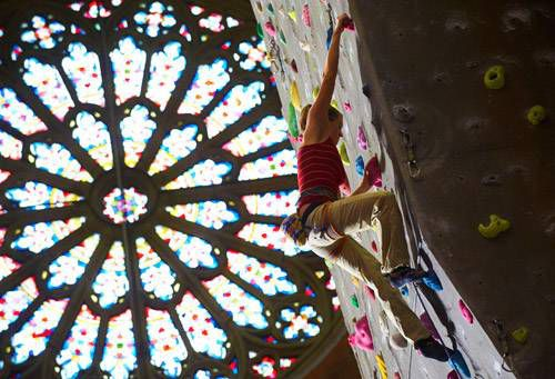 Person climbing up a rock wall with a huge stained glass window in the background