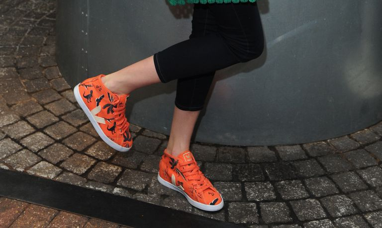 Person showing off brightly colored sneakers featuring an animal print