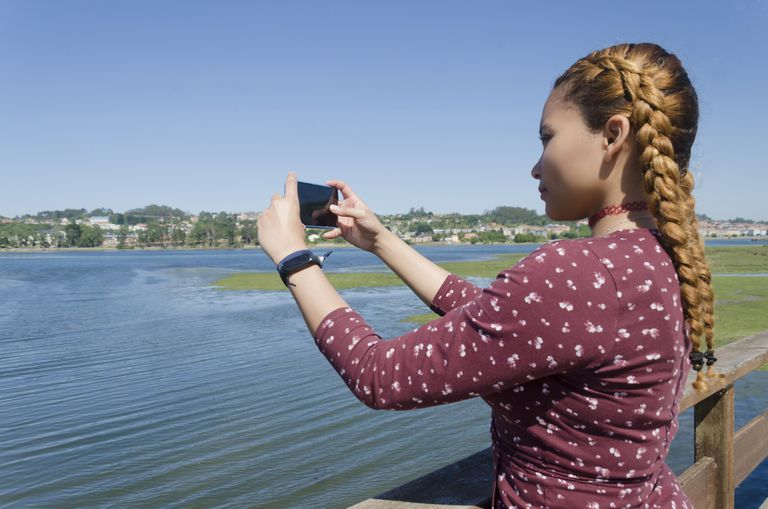 Young woman with her hair in two braids taking a picture of the water