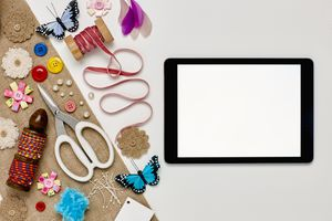 A flatlay of a tablet with sewing and craft materials on a table.