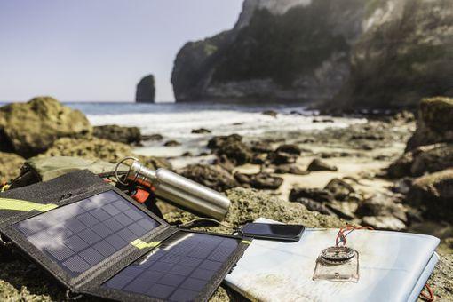 Portable solar panel charging a laptop near the ocean.