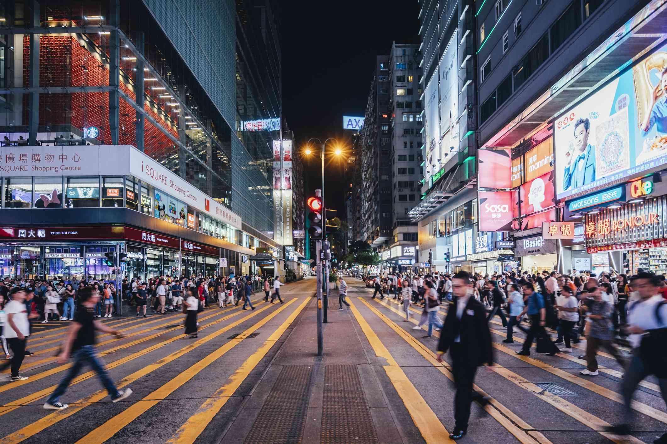 People crossing Nathan Road, Hong Kong, at night