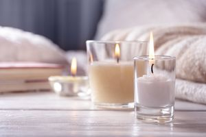 Home interior. Still life with detailes. Several candles on white wooden table in front of bed, the concept of cosiness.