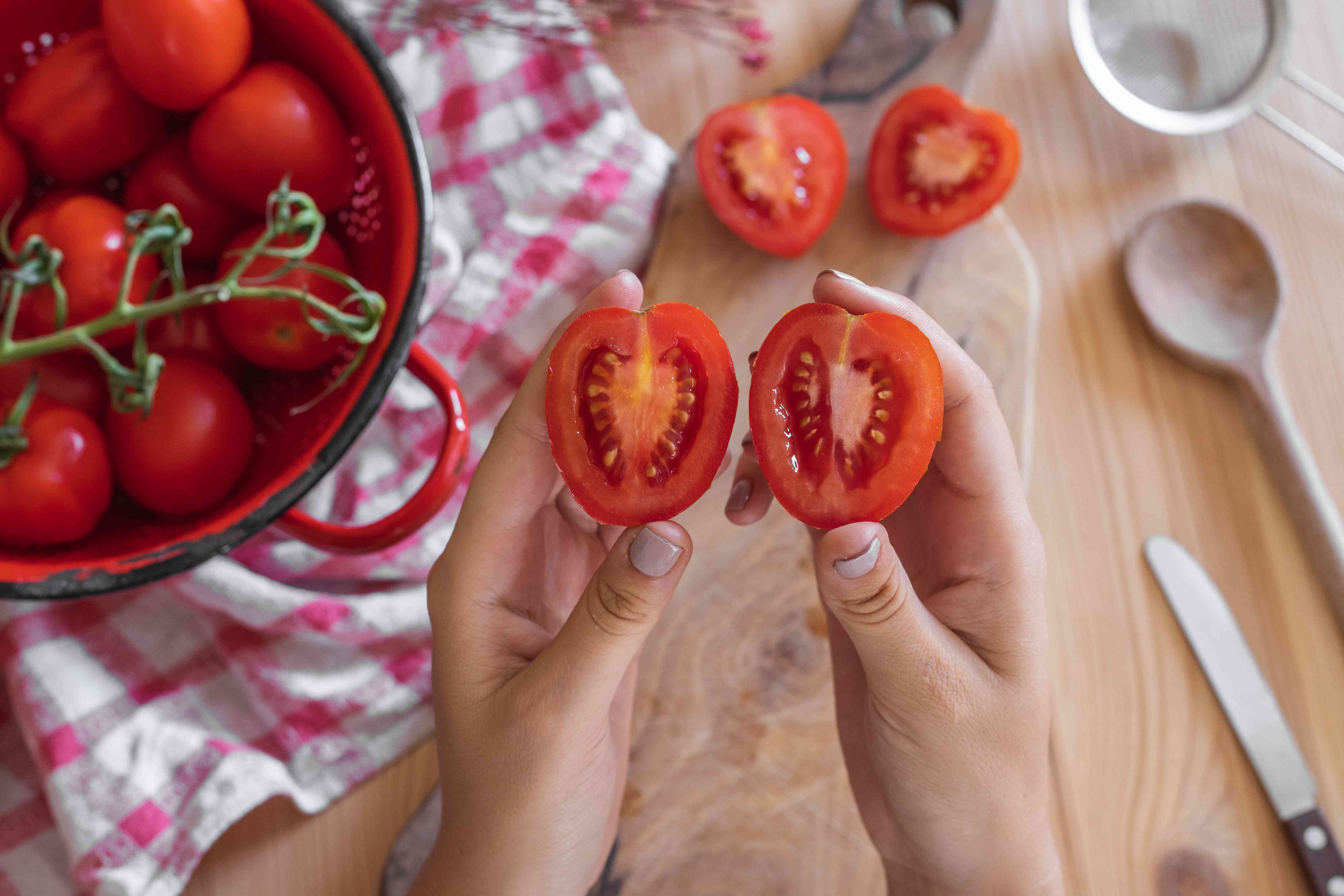 hands hold up small tomato cut in half, with kitchen tools and tomatoes on wooden table