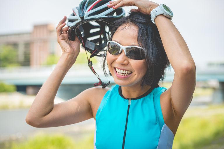 An Asian woman takes a cycling helmet off of her head outdoors.