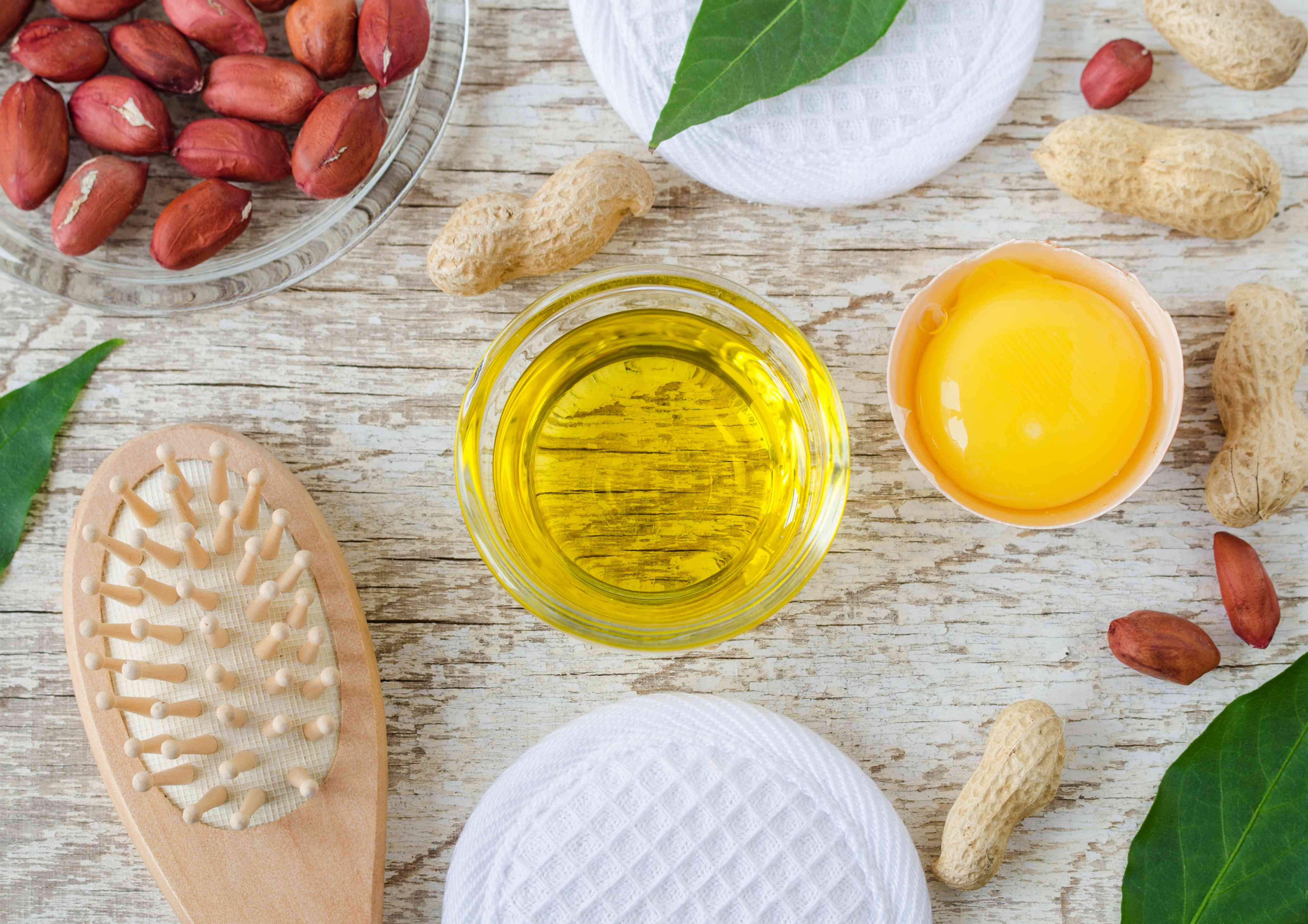 Small glass bowl with cosmetic (cleansing, massage) peanut oil, raw egg and wooden hairbrush. Natural haircare, homemade spa and beauty treatment recipe. Top view, copy space.