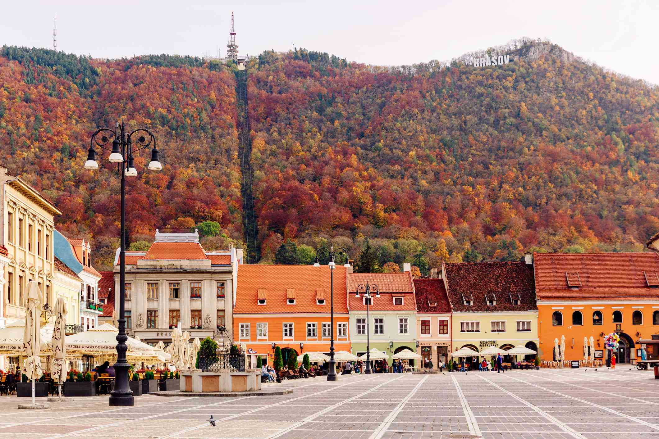 two-story, brightly colored orange, yellow, and pink buildings in Piata Sfatului square with a hill covered with trees in fall color in the background in Brasov, Romania