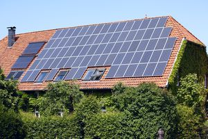 Solar panels on the rood of a house surrounded by greenery.