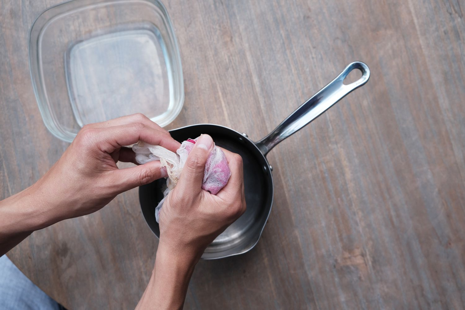 hands squeeze cheesecloth filled with wet rose petals to get out diy rose water