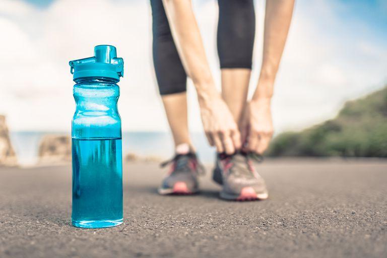 female runner ties a shoelace near a water bottle