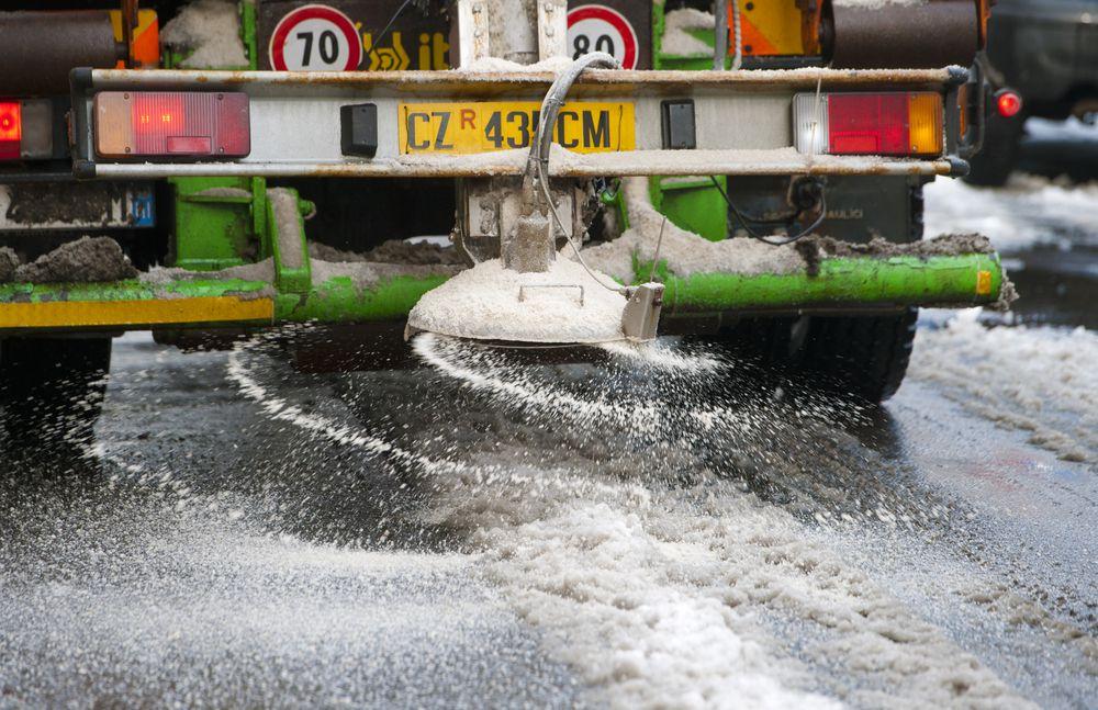 salt truck puts down salt in the snow