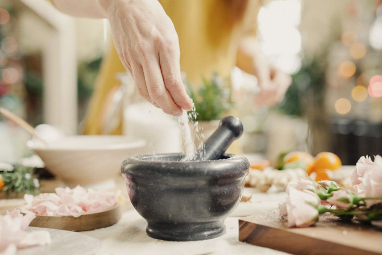 A woman adding sugar to a pestle surrounded by roses in a kitchen.