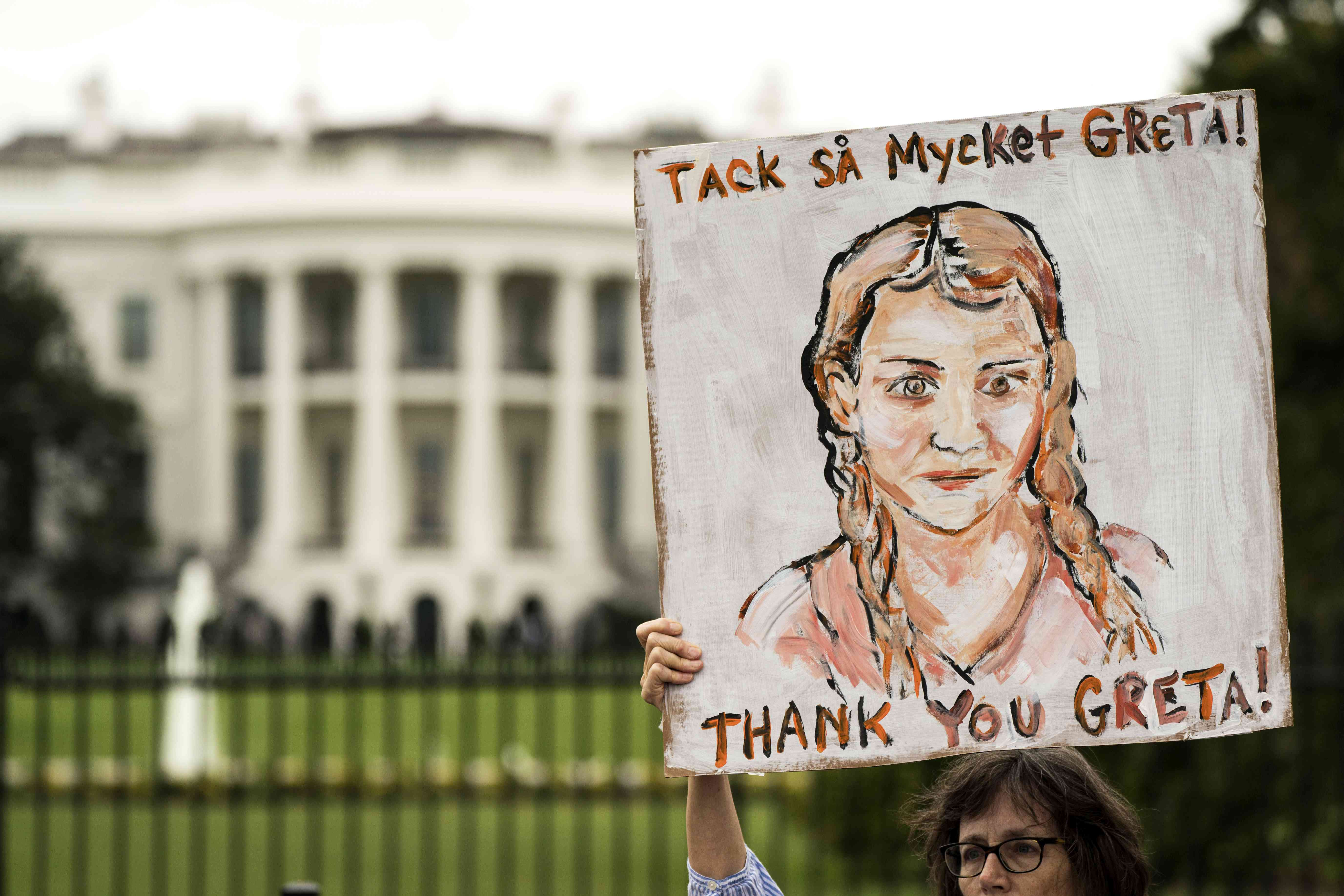 woman holds sign with a sketch of Greta Thunberg to demand climate action