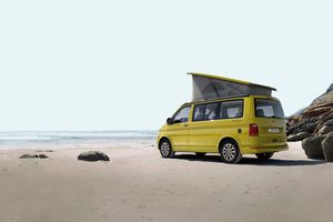 Yellow van with elevated camper top parked on the beac