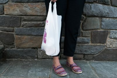 shot of woman in pants holding plastic bag