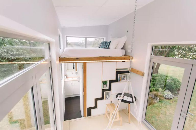 Sleeping loft and storage wall with hidden staircase in a tiny home