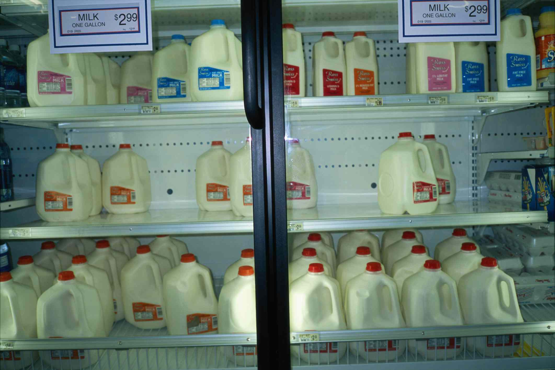 Milk jugs in a fridge at a store with signs.