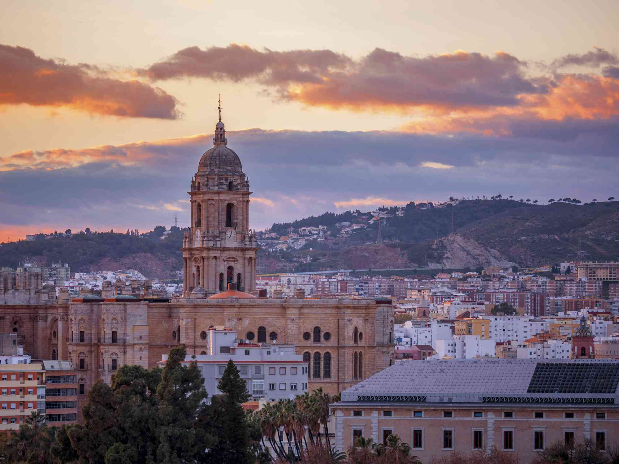 dome of cathedral in Malaga rises above the city in Spain as the sun begins to set