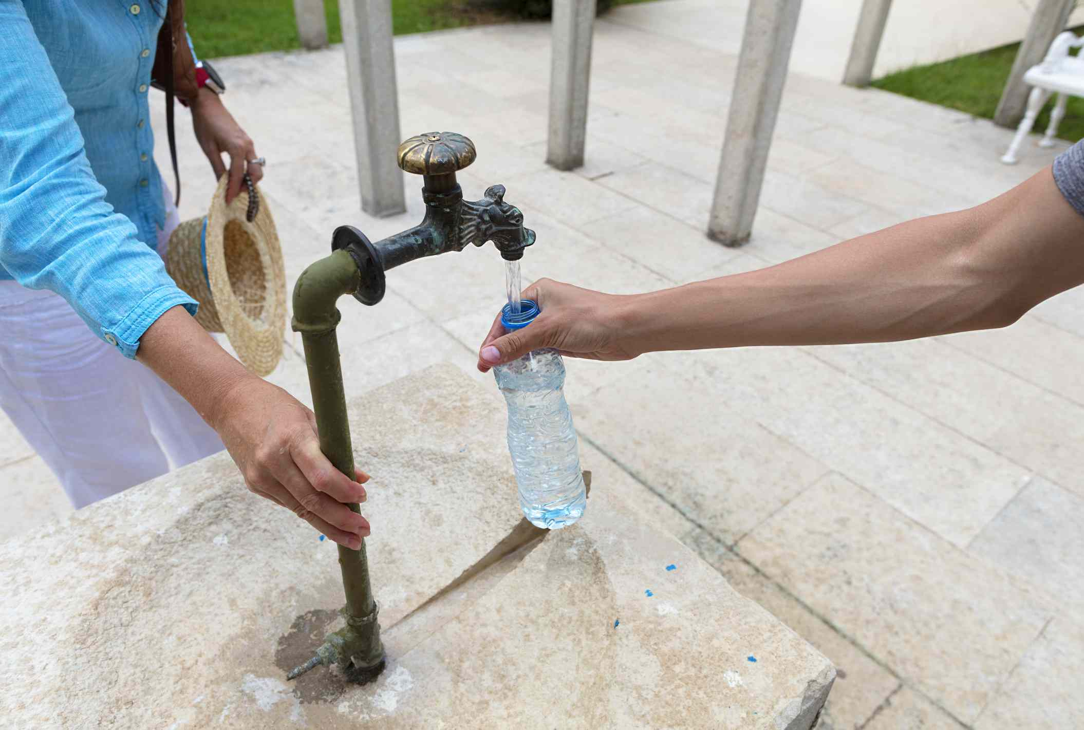 A person refilling a plastic water bottle with tap water.