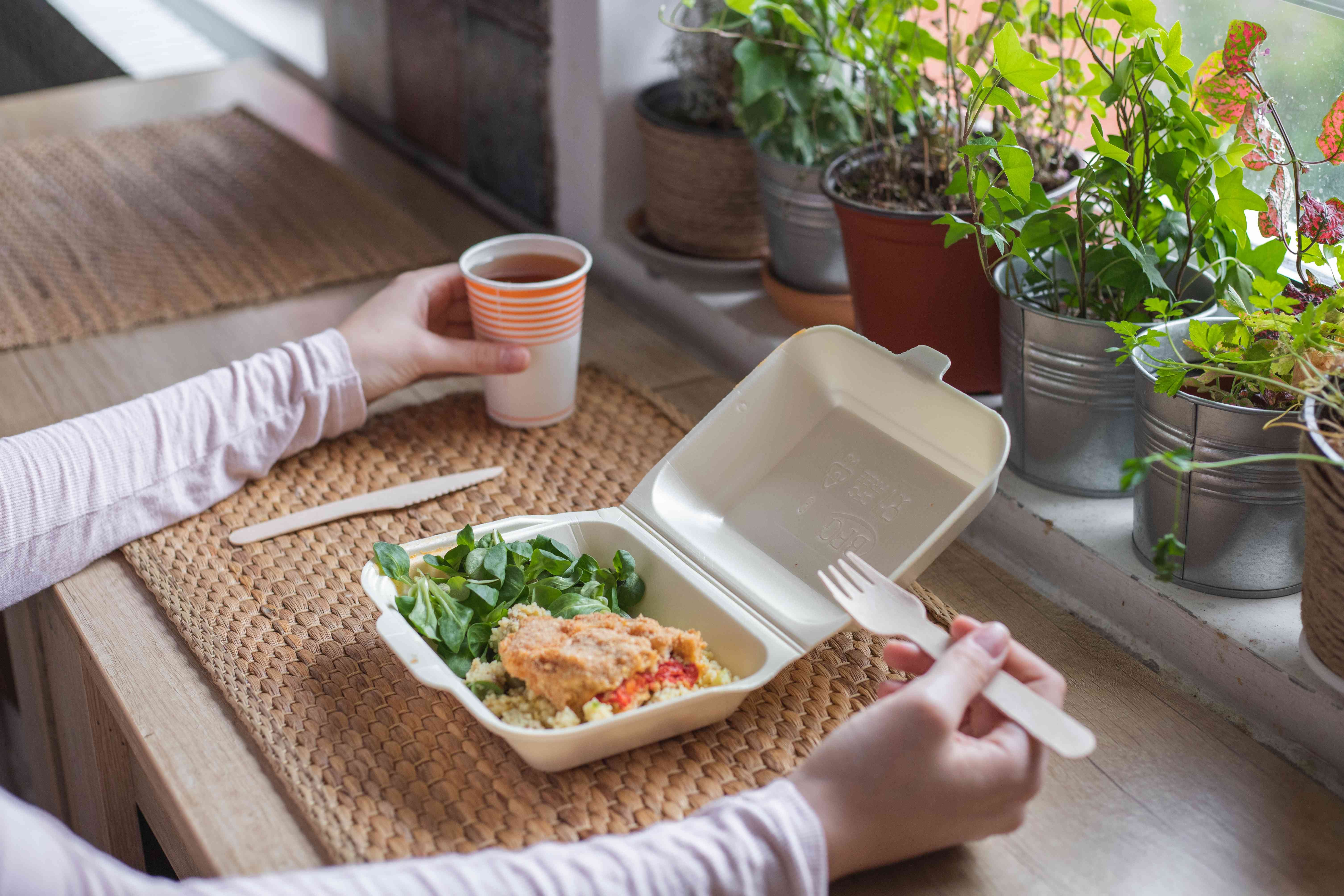 person sits at window for lunch with biodegradable and disposable plastic containers, fork and cup